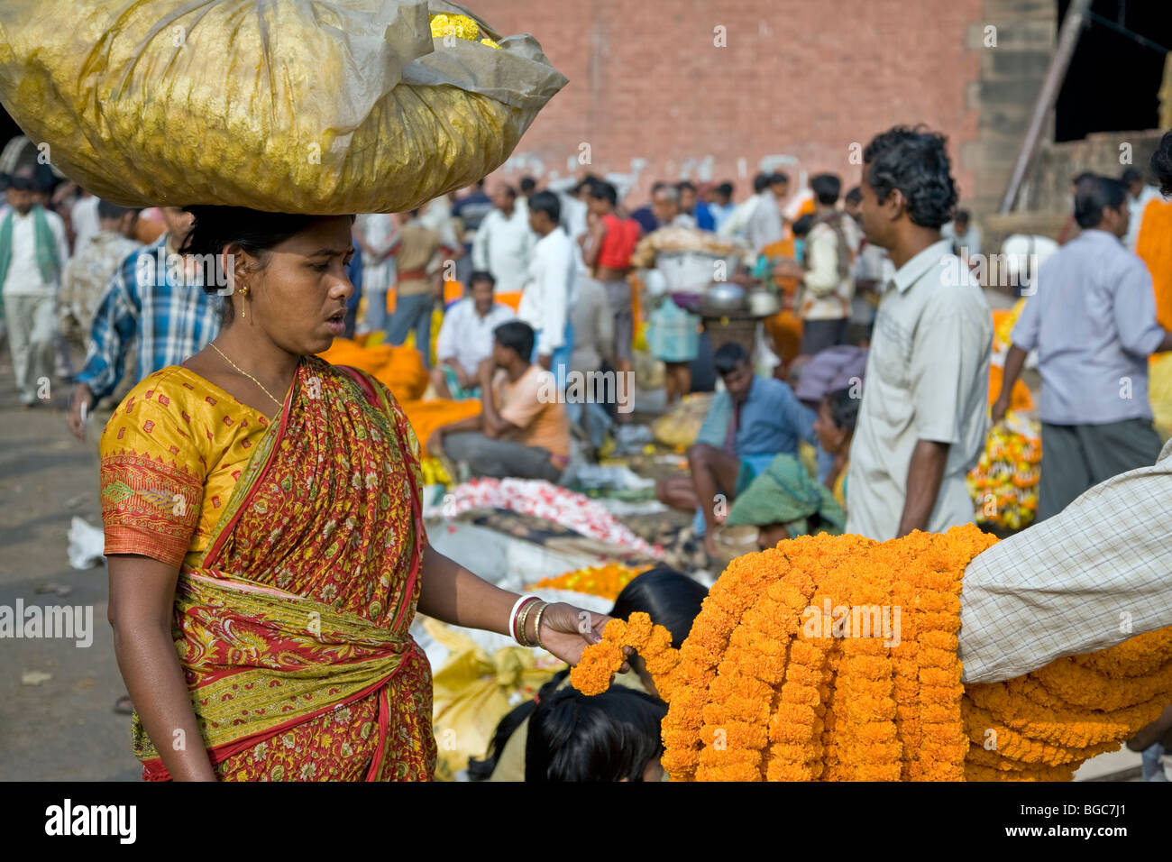 Indian woman checking the flower garlands. Flowers market. Calcutta (Kolkata). India - Stock Image