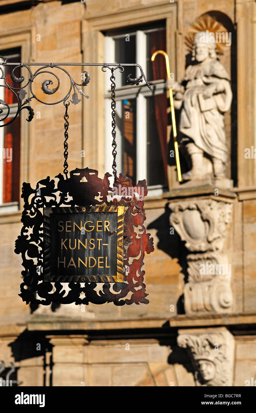 Decorative hanging sign of the art store 'Senger', in the back the figure of a saint on a façade, Karolinenstrasse, - Stock Image