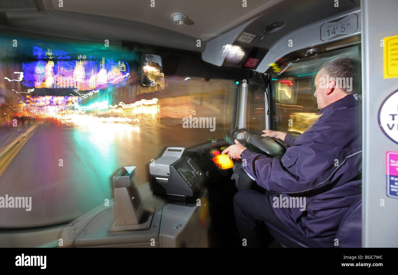 Bus driver in the Uk driving his public service vehicle bus at night in a city - Stock Image
