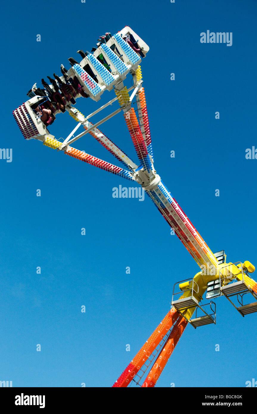 Freak Out fairground ride at top of pendulum swing , against blue sky , Tavistock Goose Fair , Devon , England - Stock Image