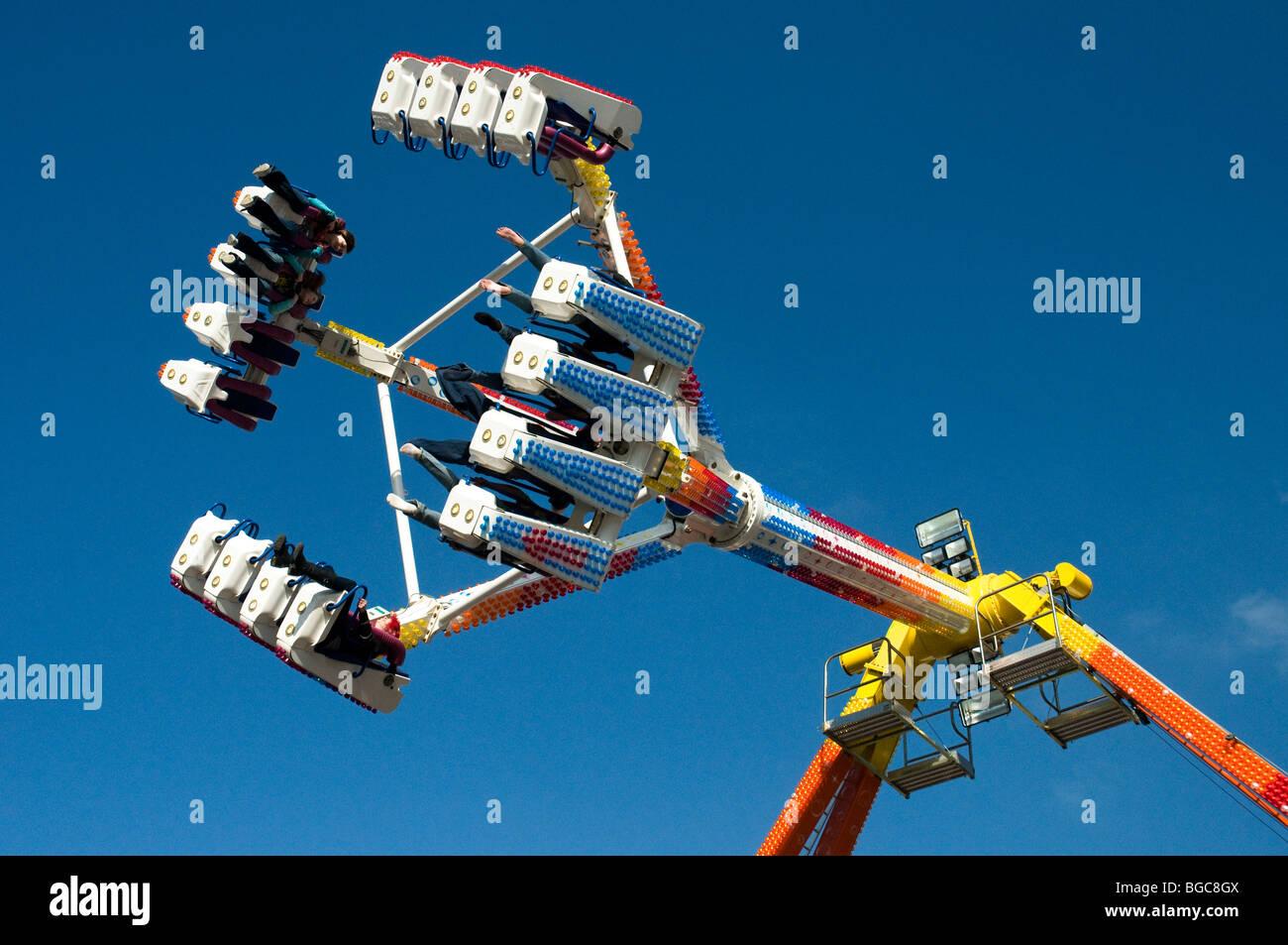 Freak Out fairground ride during pendulum swing , against blue sky , Tavistock Goose Fair , Devon , England - Stock Image