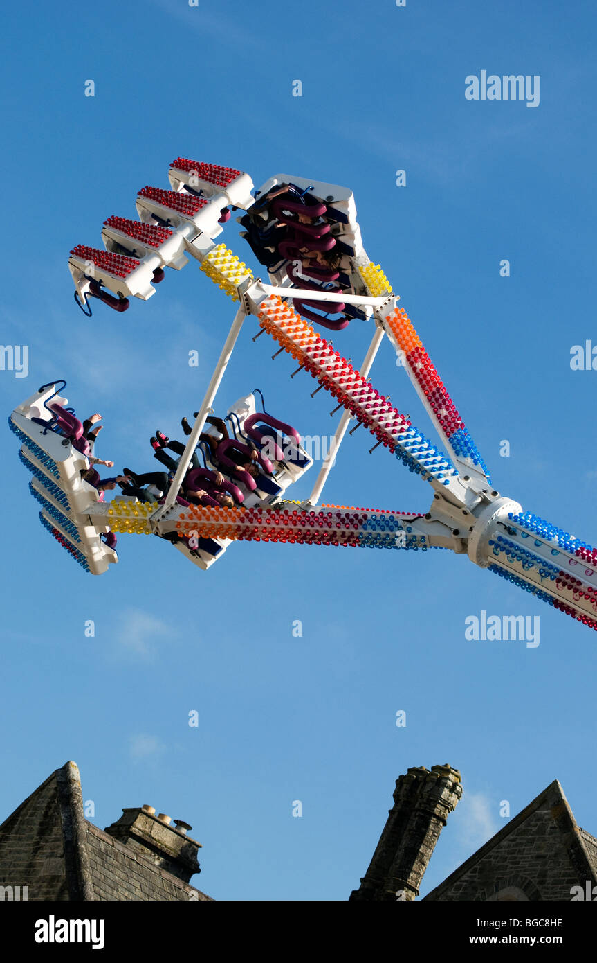 Freak Out fairground ride at top of pendulum swing framed on an angle with roofs and chimneys below, Tavistock Goose - Stock Image