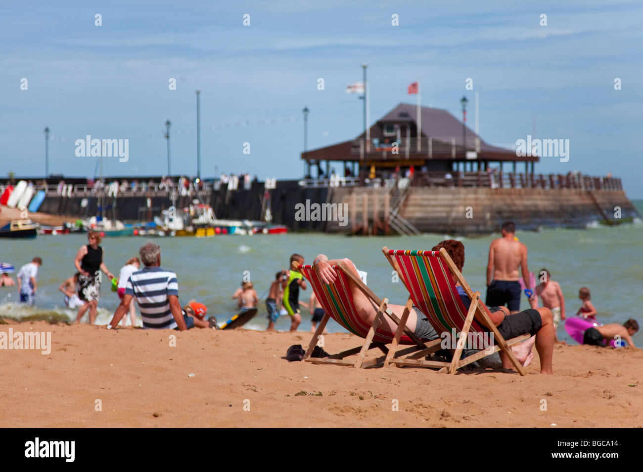 A couple relaxing on deck chairs at Broadstairs Beach, Kent, England on a lovely sunny Summer day. - Stock Image