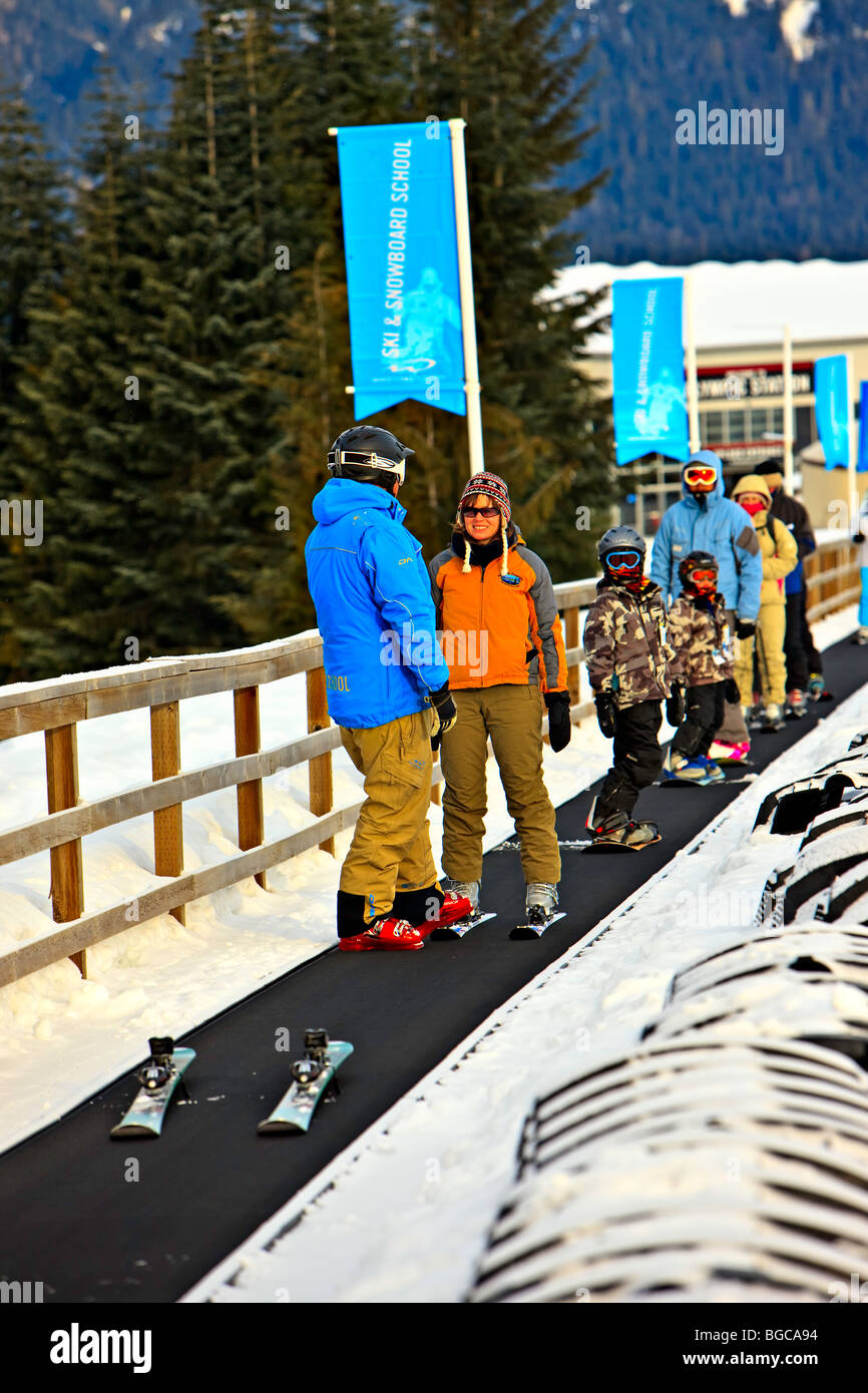 Ski Instructor and student on the magic carpet lift on the beginners slope of Whistler Mountain, Whistler Blackcomb, - Stock Image