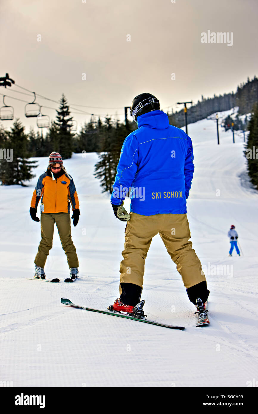 Ski instructor with a student on the beginners slope of Whistler Mountain, Whistler Blackcomb, Whistler, British - Stock Image