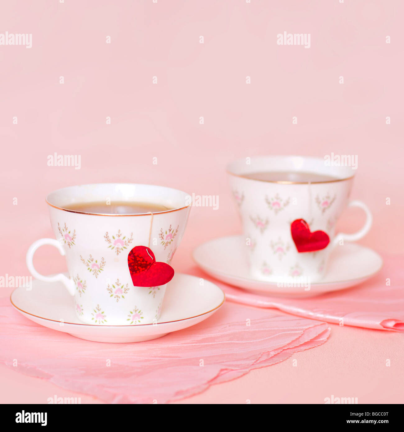 two cups with hearts on the pink background - Stock Image