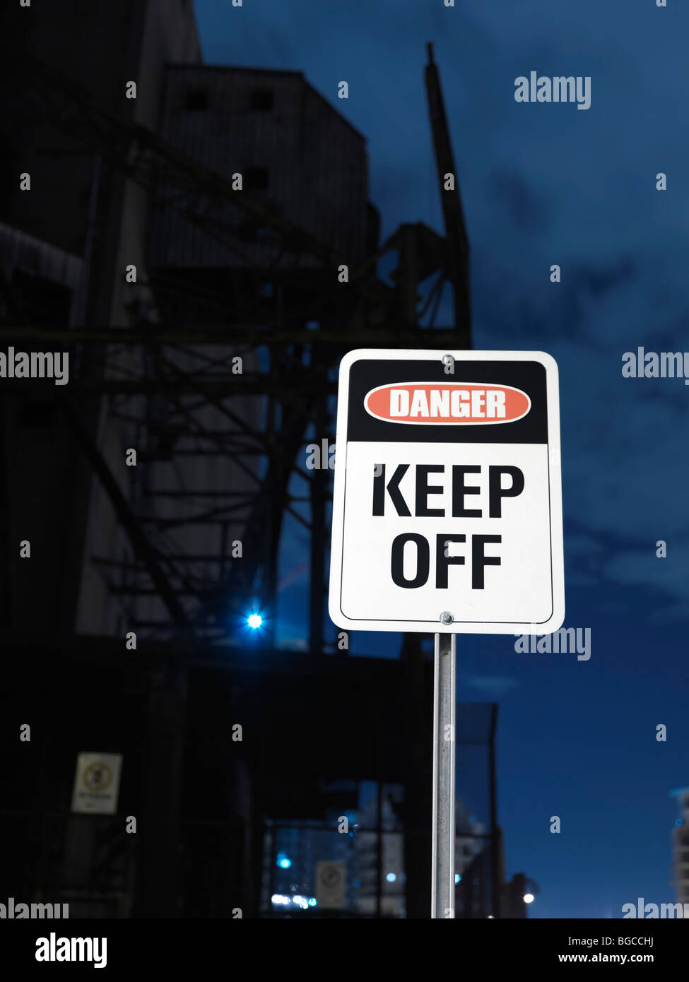 Danger - Keep Off sign with an industrial building in the background - Stock Image