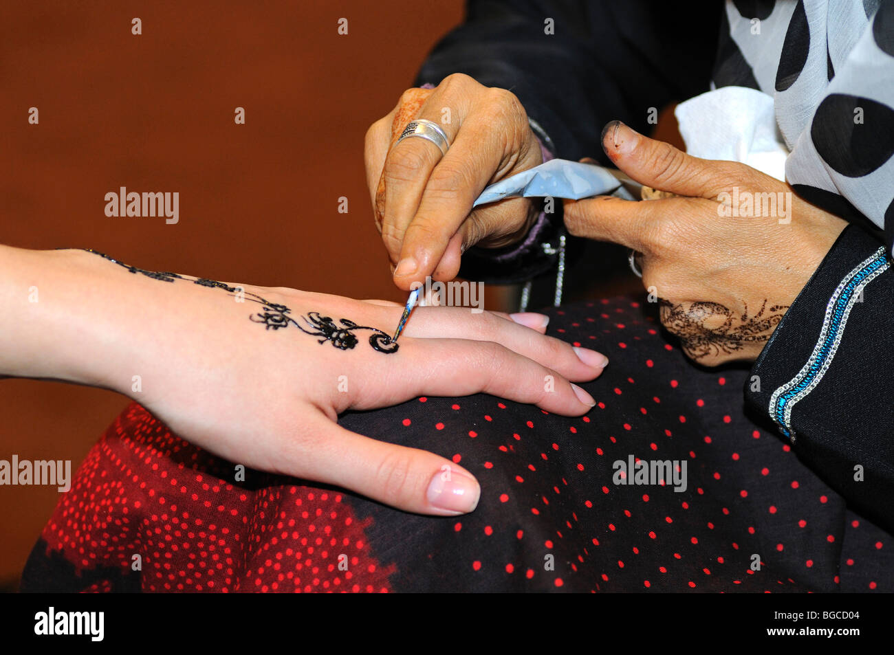 Arab Woman Applies Henna Paste On A Hand To Draw A Henna Tattoo