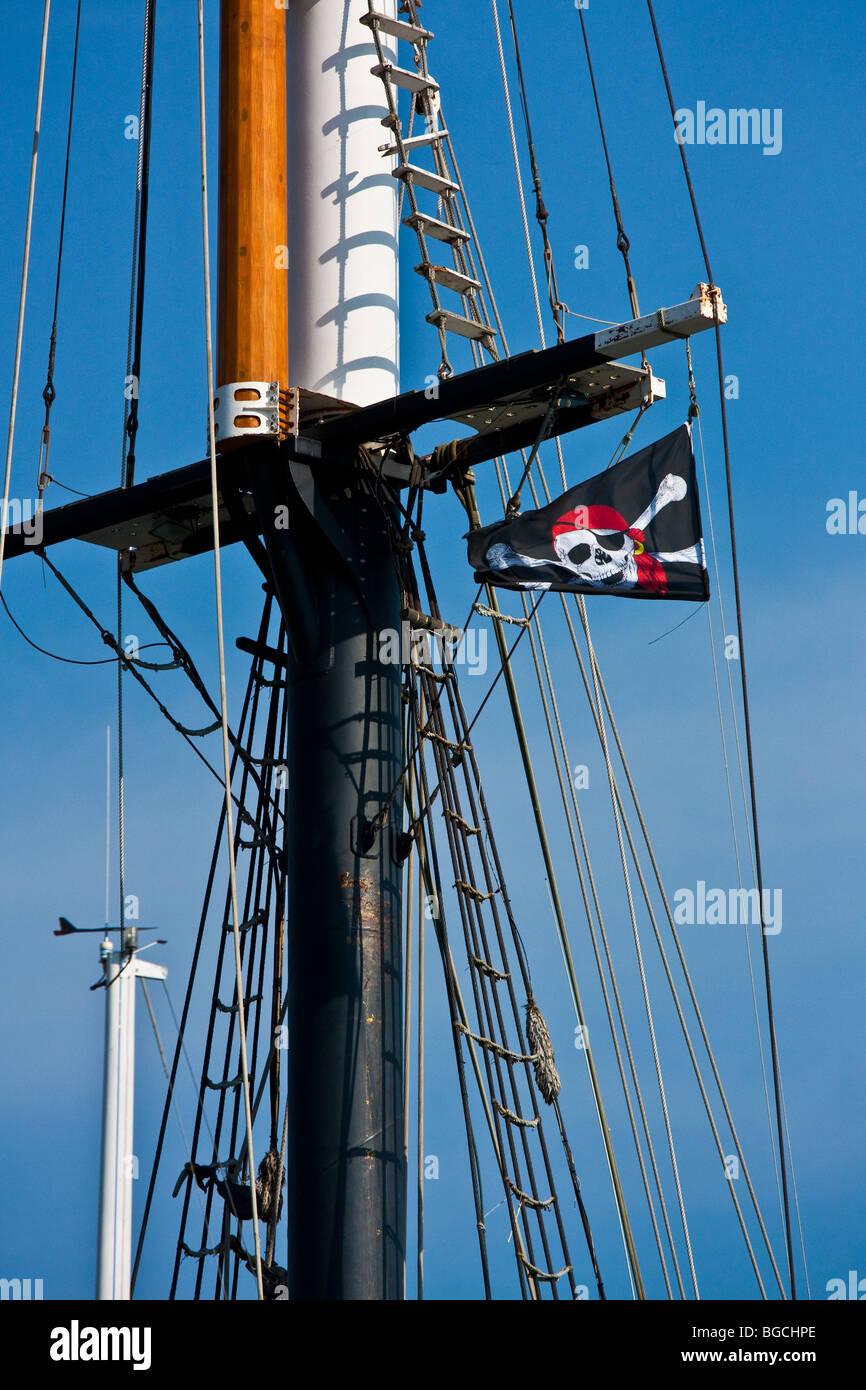 Raised pirate flag on a ship mast - Stock Image