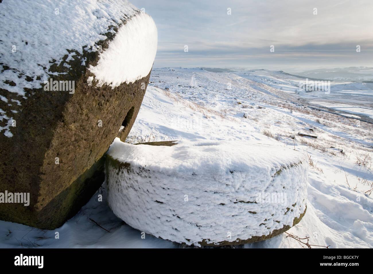 "Two Millstones in Winter Snow under "" Stanage Edge"" in the ""Peak District"", Derbyshire, United Kingdom, Great Britain Stock Photo"