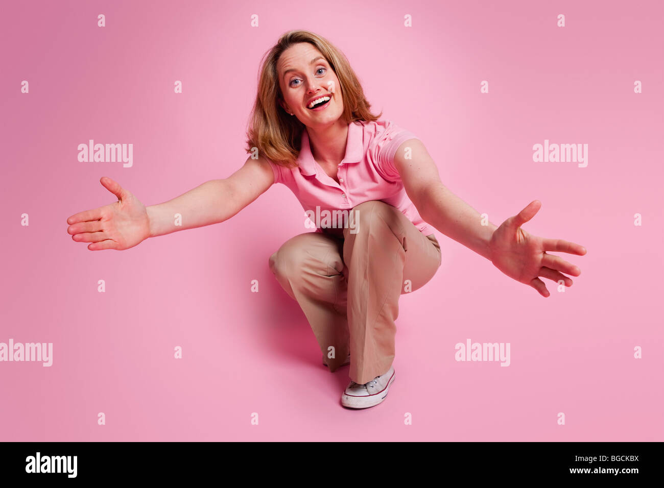 Crouching woman with outstretched open arms on pink background - Stock Image