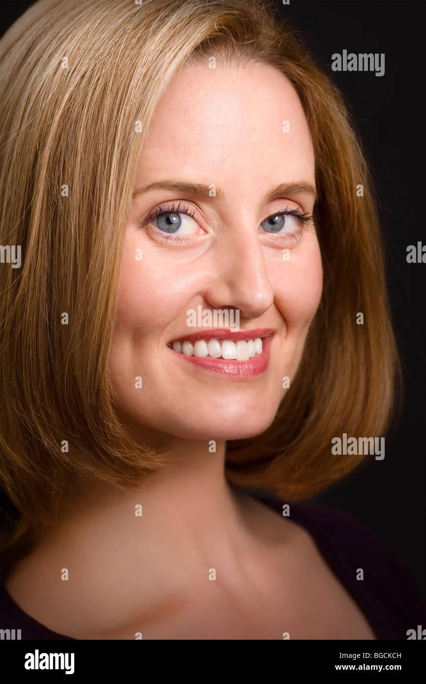 Glamorous blue-eyed woman smiling to camera - Stock Image