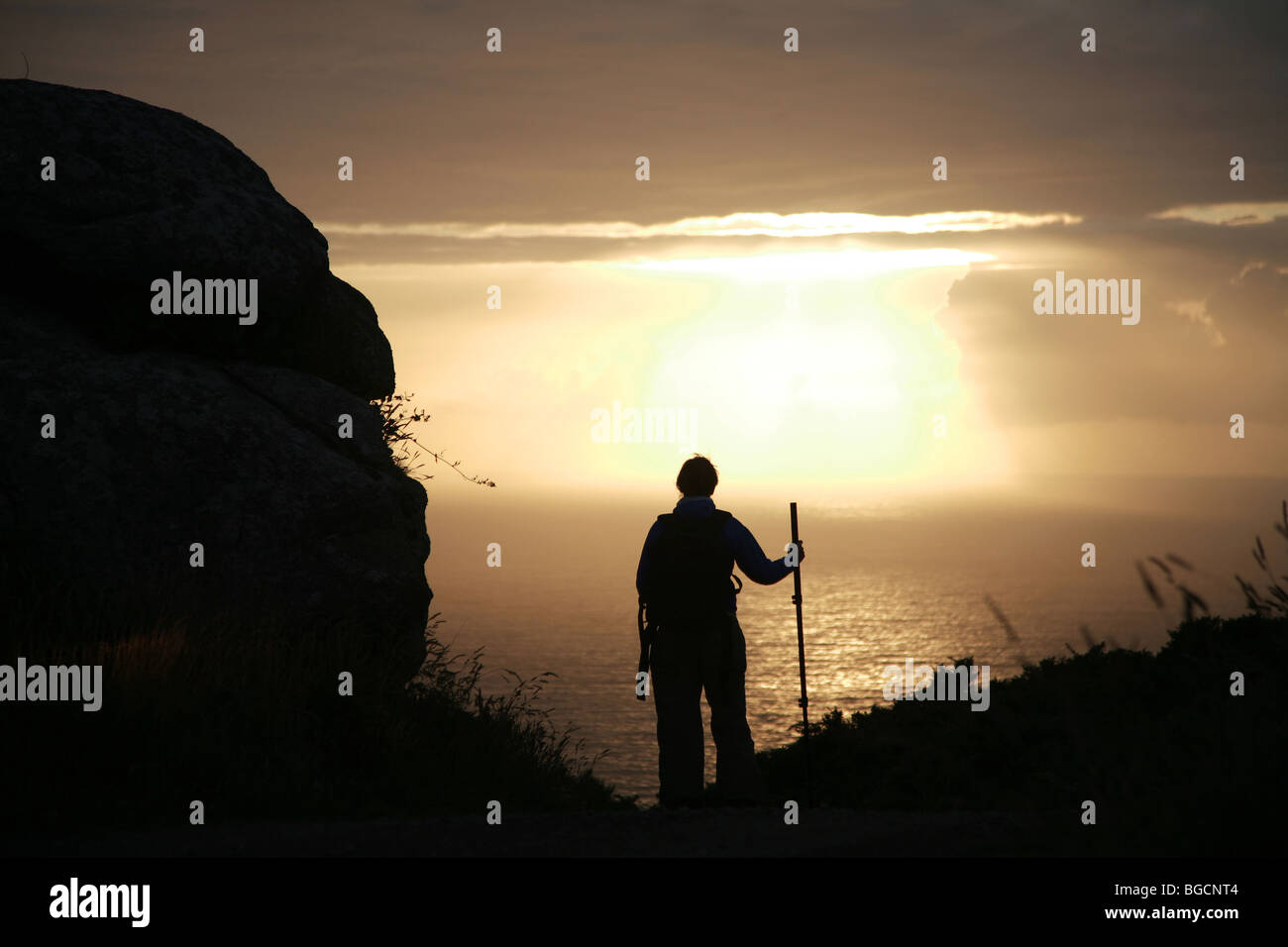 Sunset and girl at Finisterre cape, Camino de Santiago - Stock Image