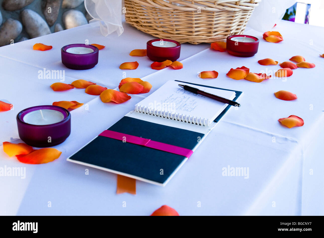 Wedding guest book with signatures on a table with flower petals and votive candles Stock Photo
