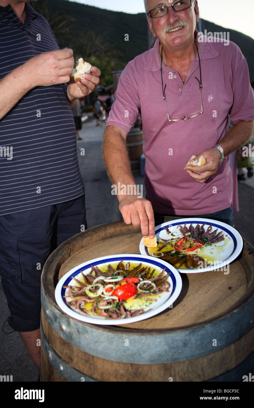 Middle aged man tastes salted anchovies fillets served on improvised table made of old barrel. - Stock Image