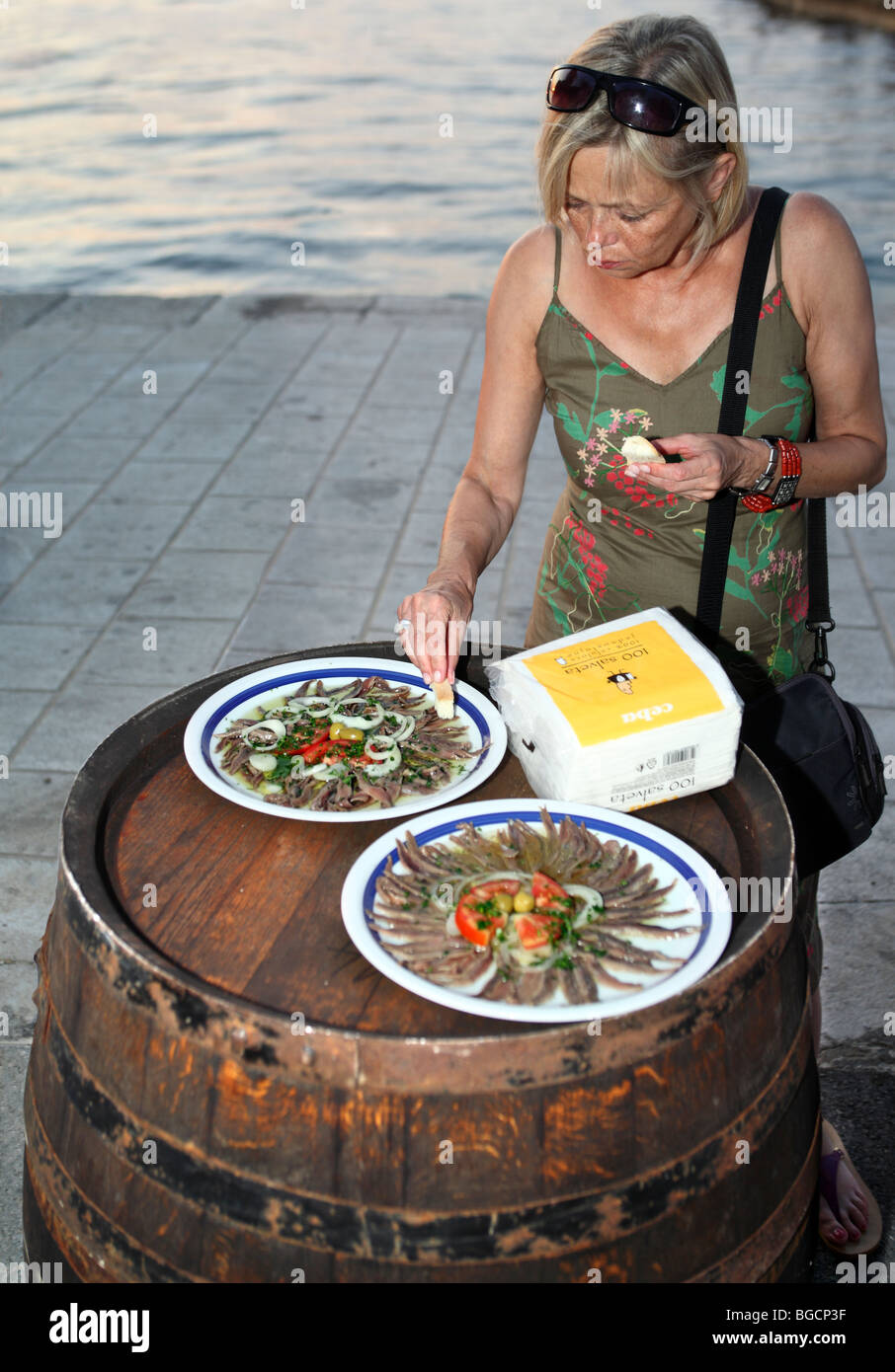 Middle aged woman tastes salted anchovies fillets served on improvised table made out of old barrel. - Stock Image