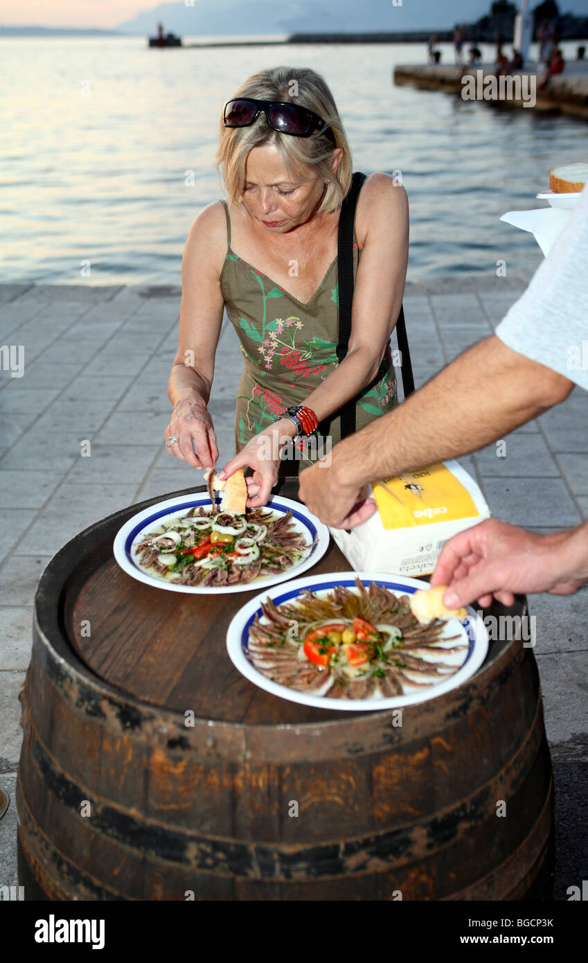 Middle aged woman tastes salted anchovies fillets served on improvised table made of old barrel. - Stock Image