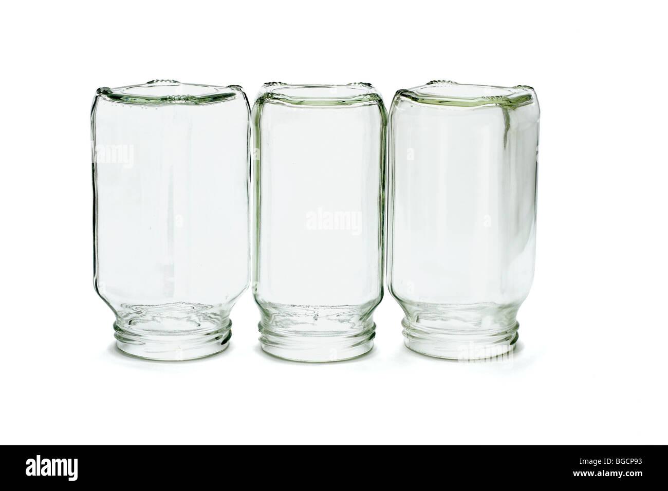 Three glass bottles inverted on white background - Stock Image
