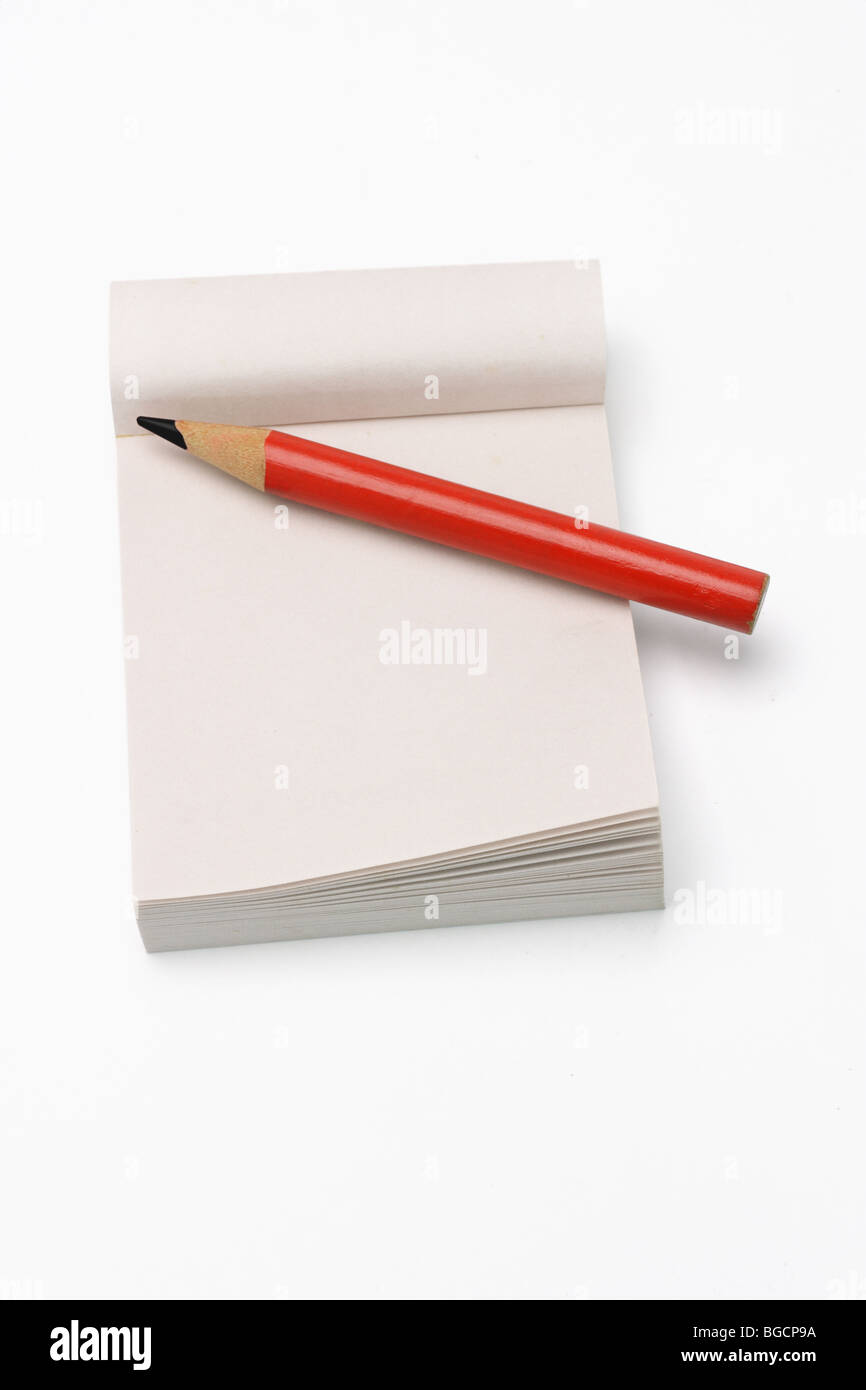 Red short pencil on mini notepad on white background Stock Photo