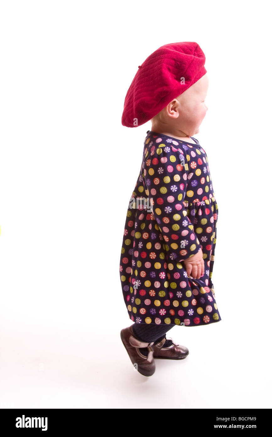 1 year old little girl wearing big red beret walks away isolated on white 7931a93db0f
