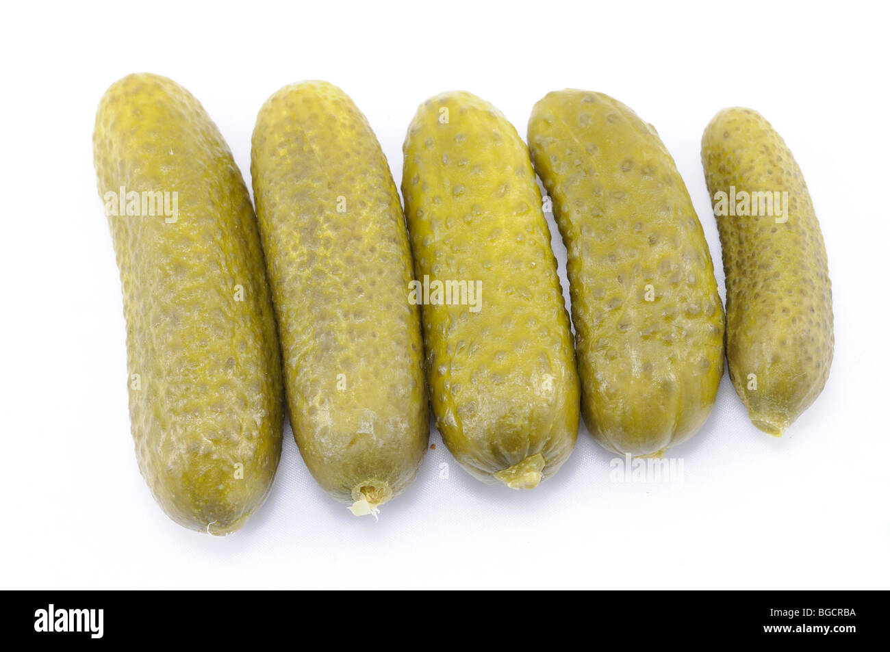 Salty pickled cucumbers isolated over white - Stock Image