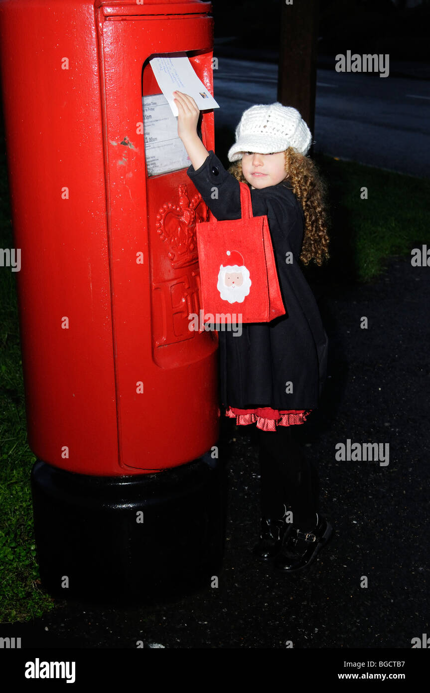 Little girl posting a letter to Santa Claus - Stock Image