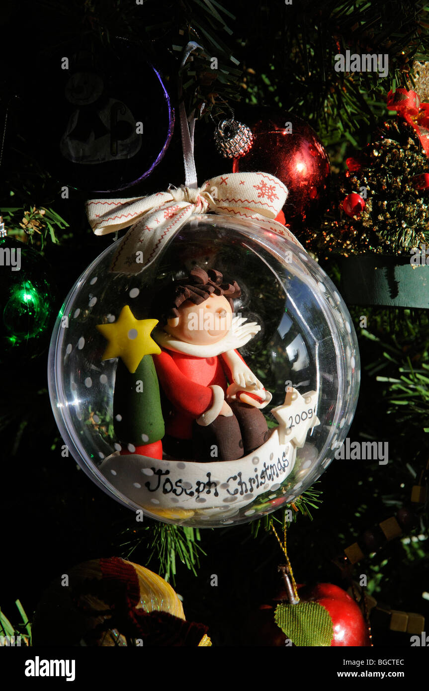 a personalised christmas bauble containing a handcrafted figure of a child called joseph hangs on a xmas tree