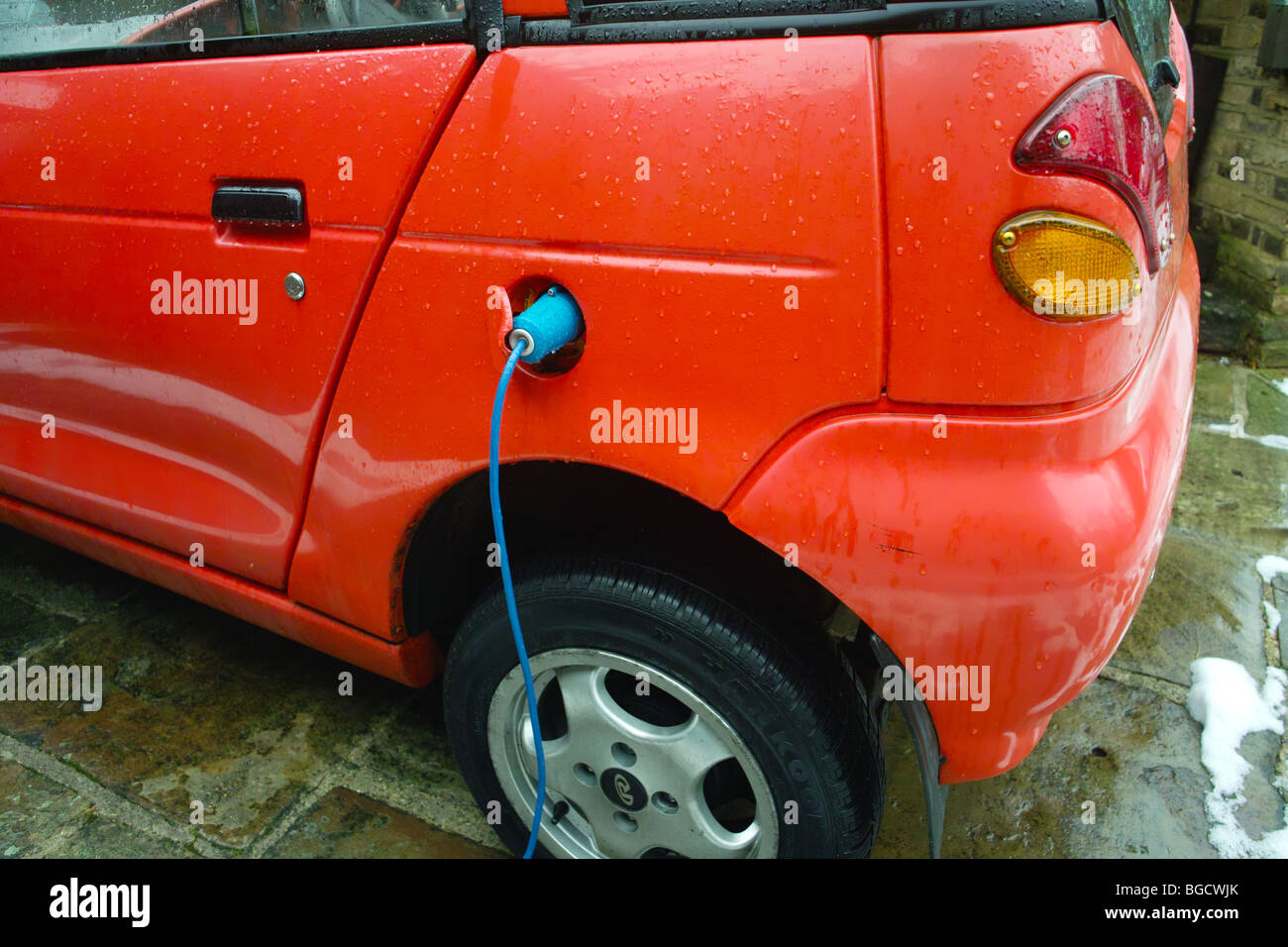 G Wiz GWiz G-Wiz clean green battery electric powered vehicle car plug plugged in charge charging recharging recharge - Stock Image