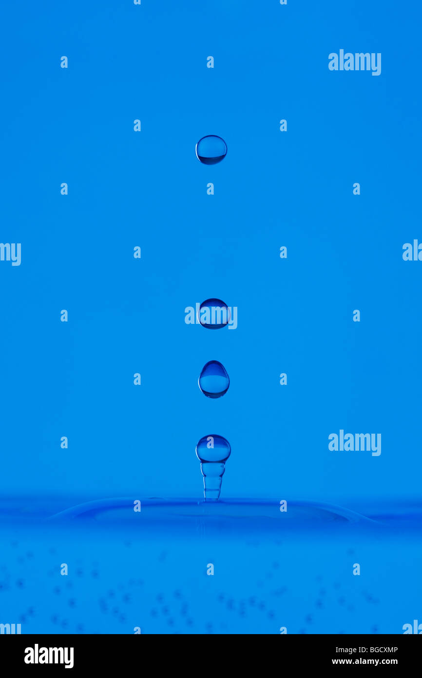 blue droplet hitting the water surface splashing it up - Stock Image