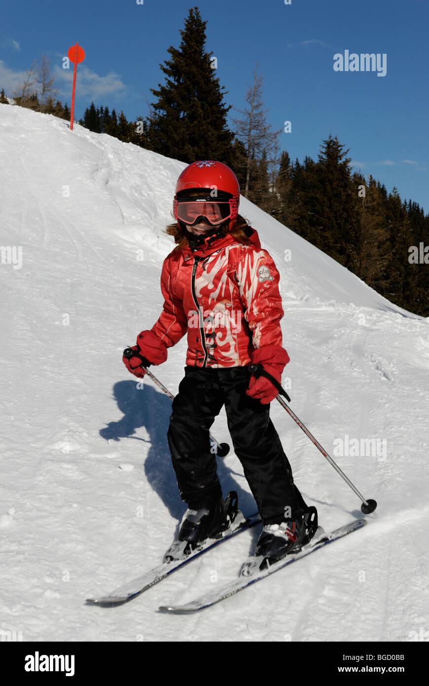Child skiing, ski-run. alpine skiing with helmet, safetyt - Stock Image