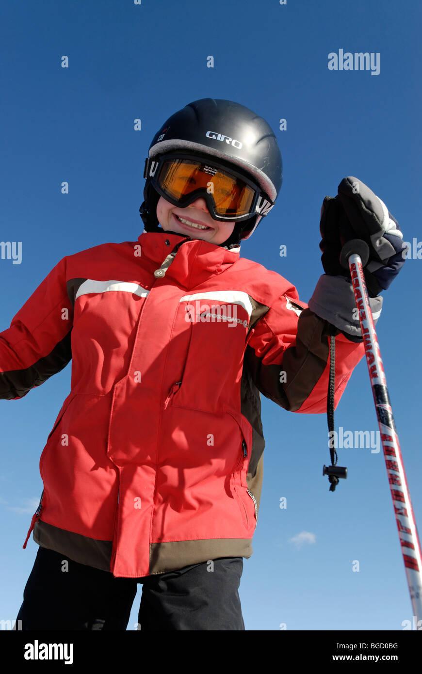 Child skiing, ski-run. alpine skiing with helmet, safety - Stock Image
