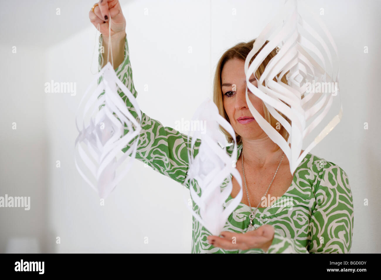Woman with a wind chime, paper mobile, creativity, artist - Stock Image