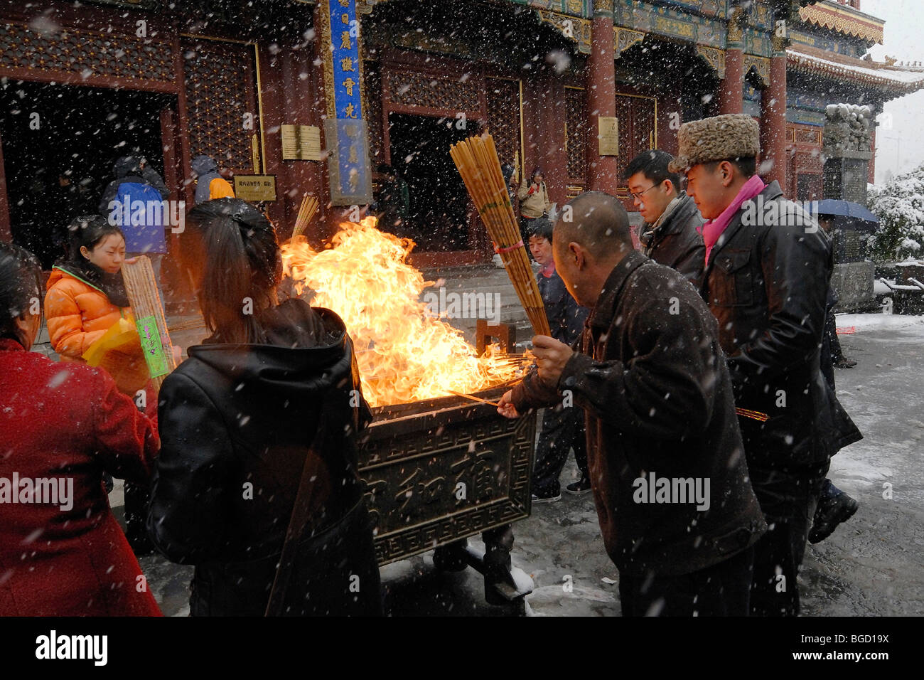 Chinese men and women lighting incense on an open fire to during heavy snowfall, snowy Buddhist Lama Temple in the Stock Photo