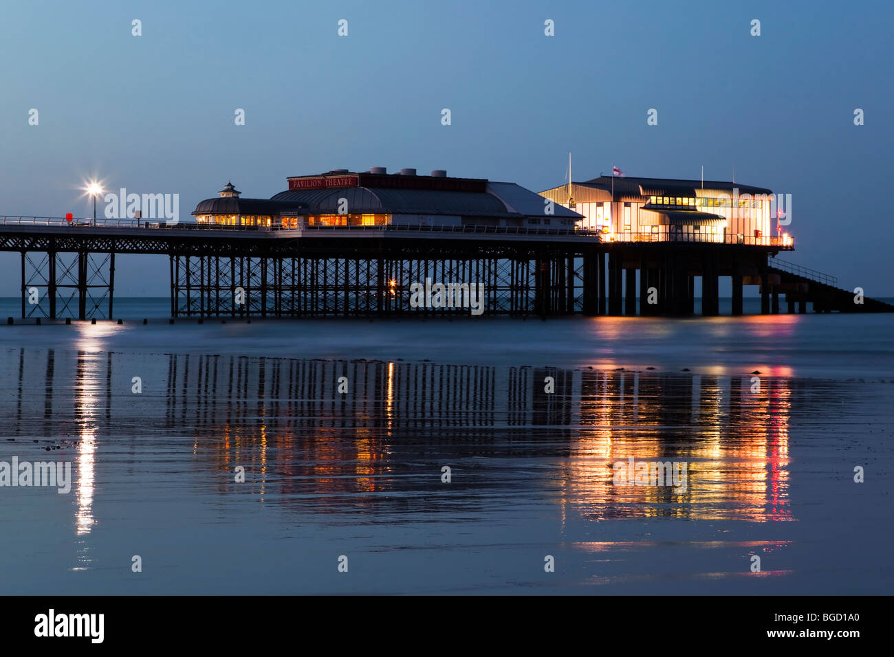 Evenings reflections in the wet sands - Cromer Pier in North Norfolk - Stock Image