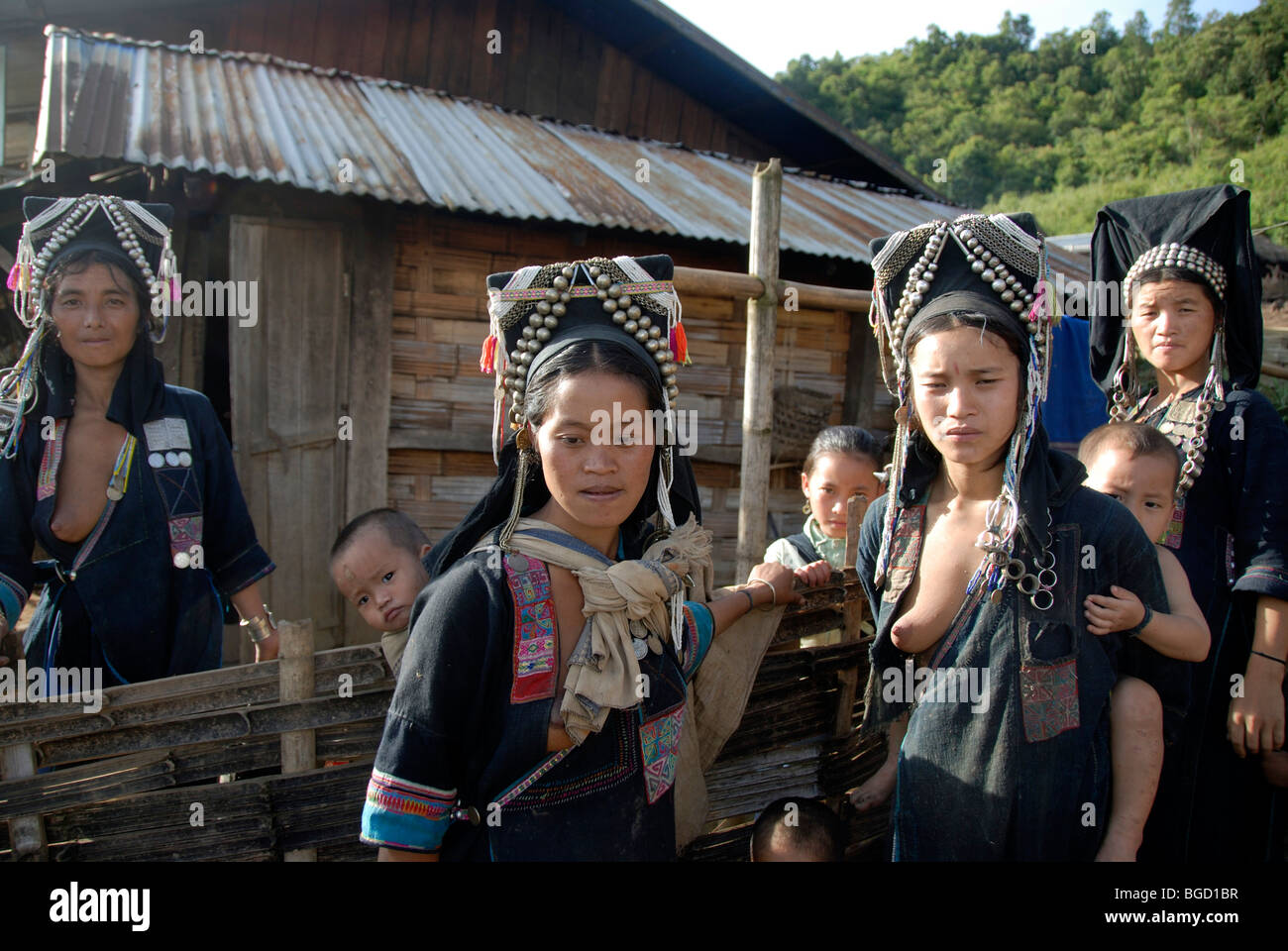 Poverty, Akha Nuqui women, with infants on their backs, dressed in indigo coloured traditional clothing and hats - Stock Image
