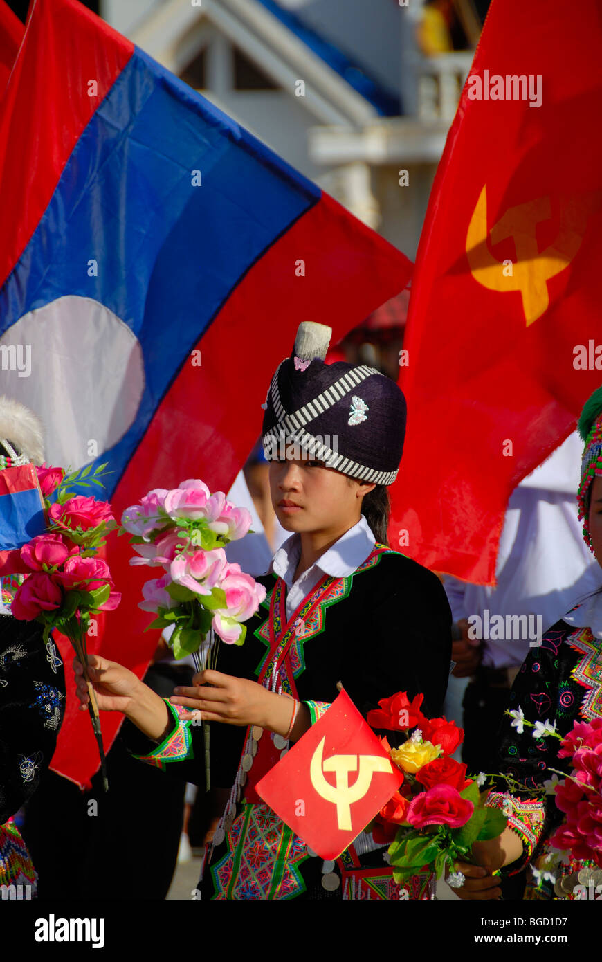 Festival, Hmong girl, dressed in traditional clothing, holding red flags of the Communist Party, national flag of Laos, Xam Neu Stock Photo
