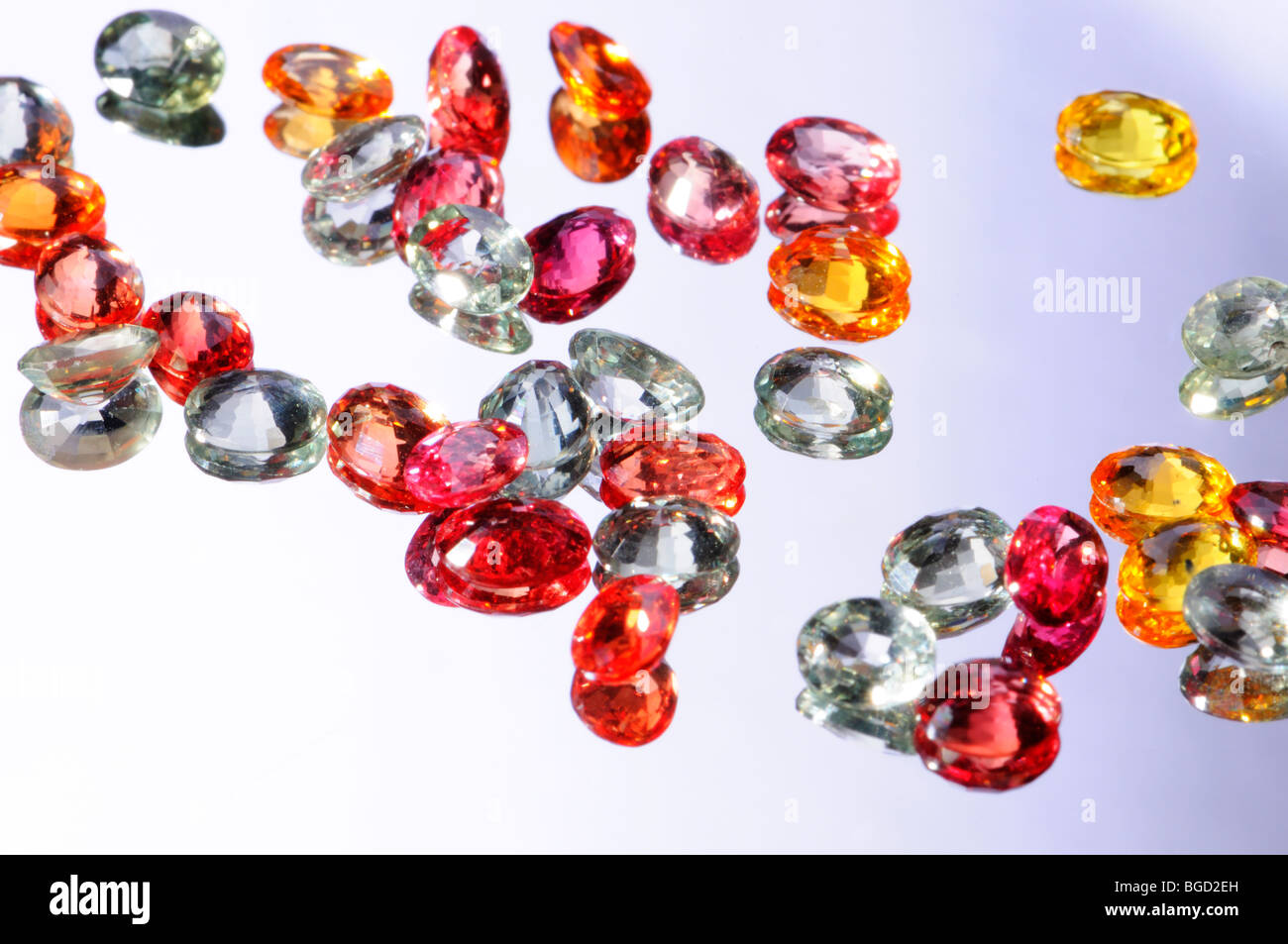 Small multi-coloured oval-cut natural sapphires - Stock Image