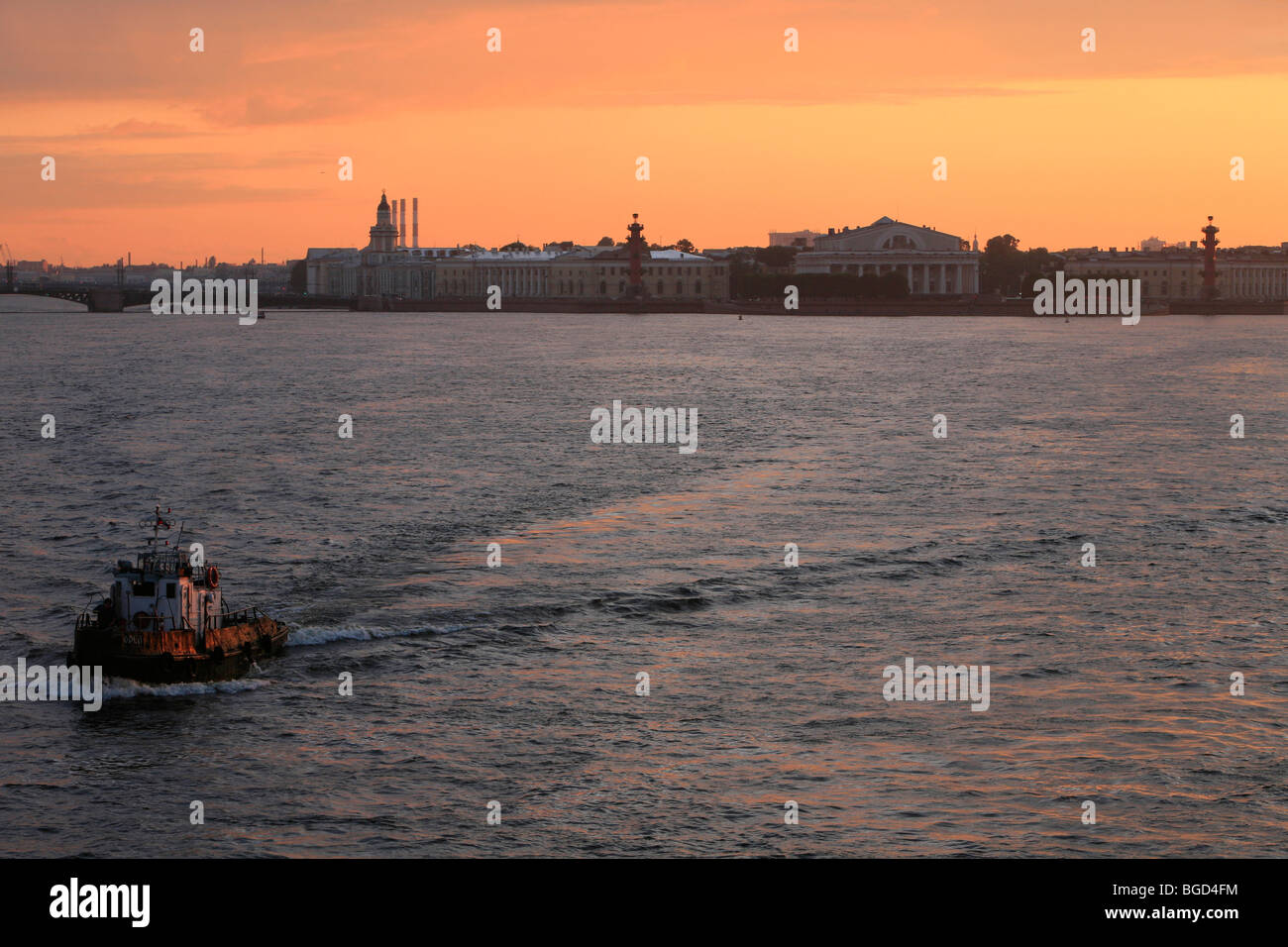 Tugboat on the Neva River with the Central Naval Museum in the background in Saint Petersburg, Russia Stock Photo