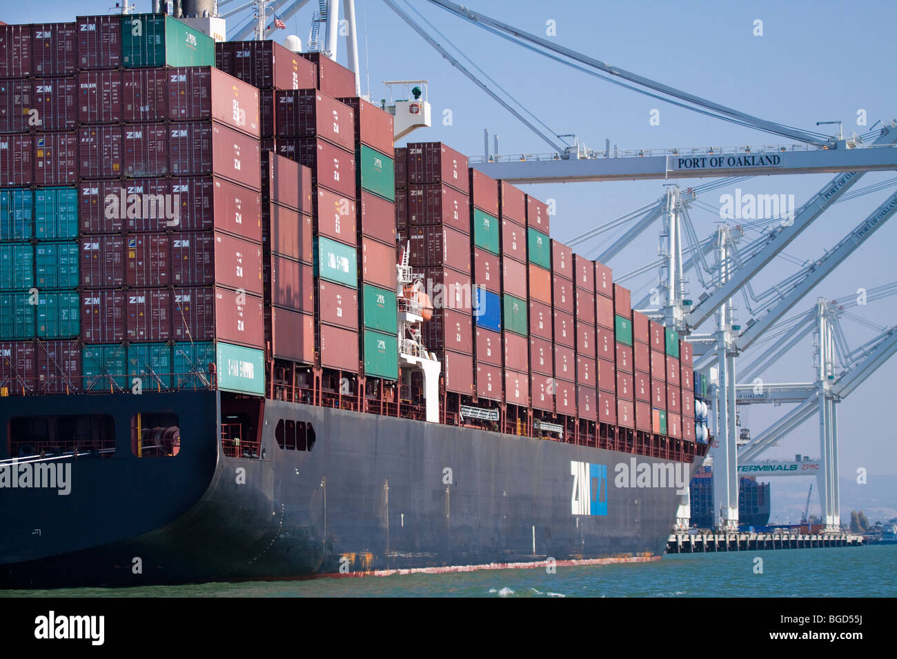 Cargo Container Ship Loaded with Portainers at Port of Oakland Docks - Stock Image