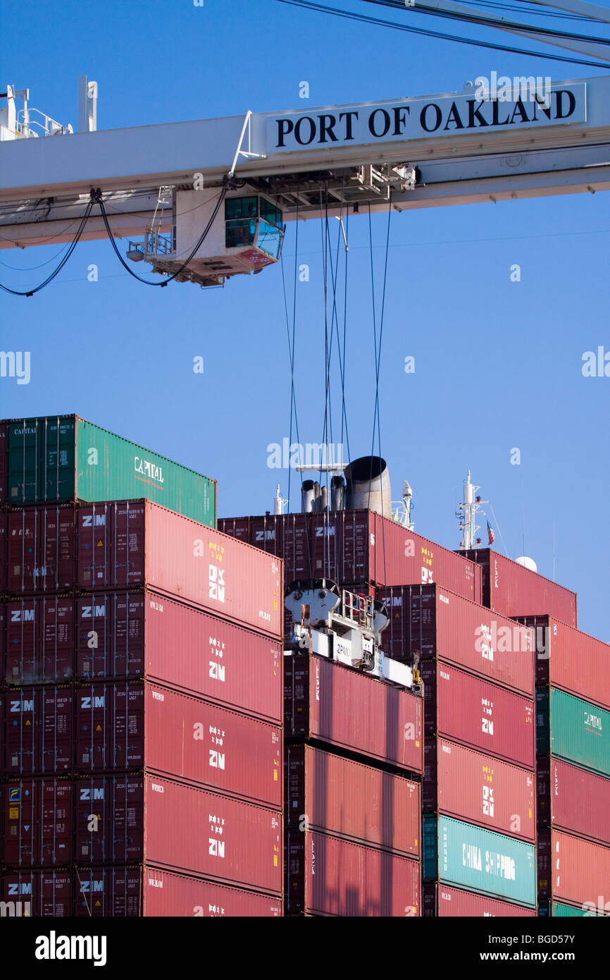 Crane lifting portainer to unload it from cargo container ship - Stock Image