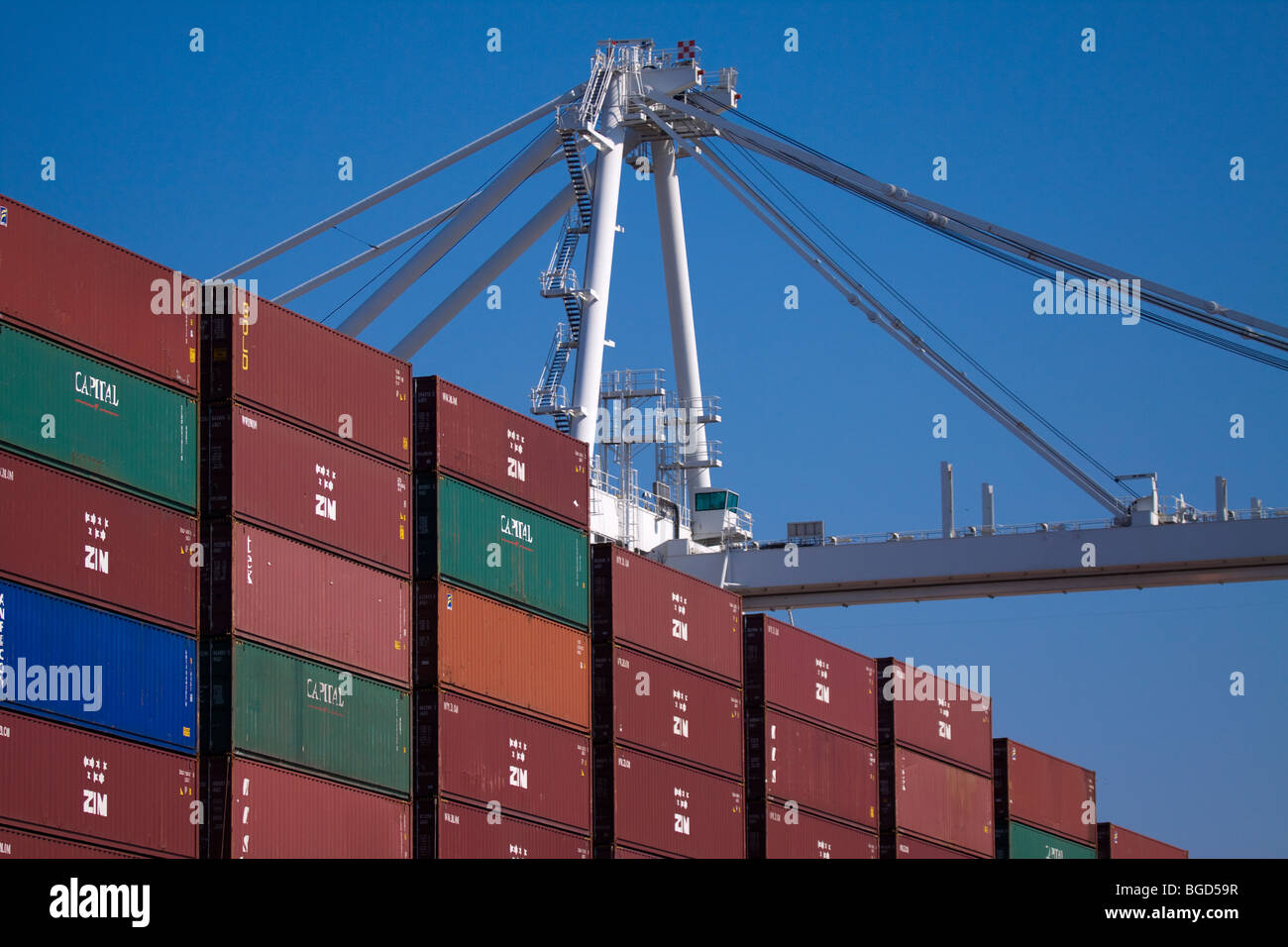 Crane and stacks of portainers on a cargo container ship Stock Photo