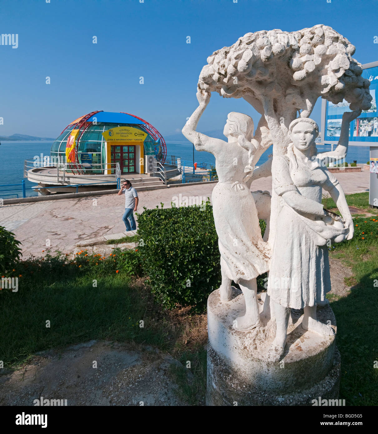 Communist era sculpture and post communist tourist office on the promenade at Saranda, in southern Albania. - Stock Image