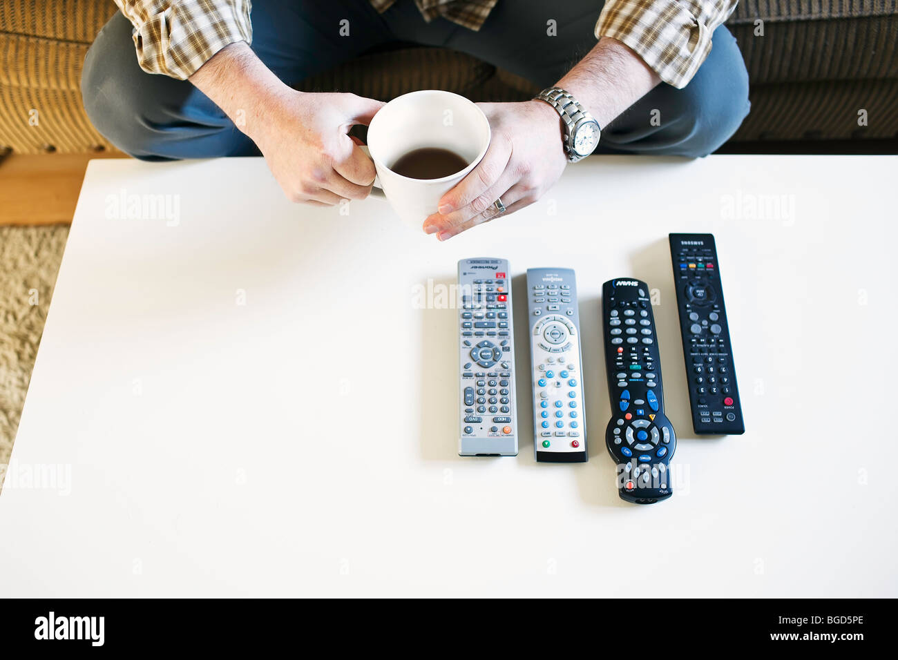 Man sitting on couch, holding coffee, with TV remote controls lined up on table. - Stock Image
