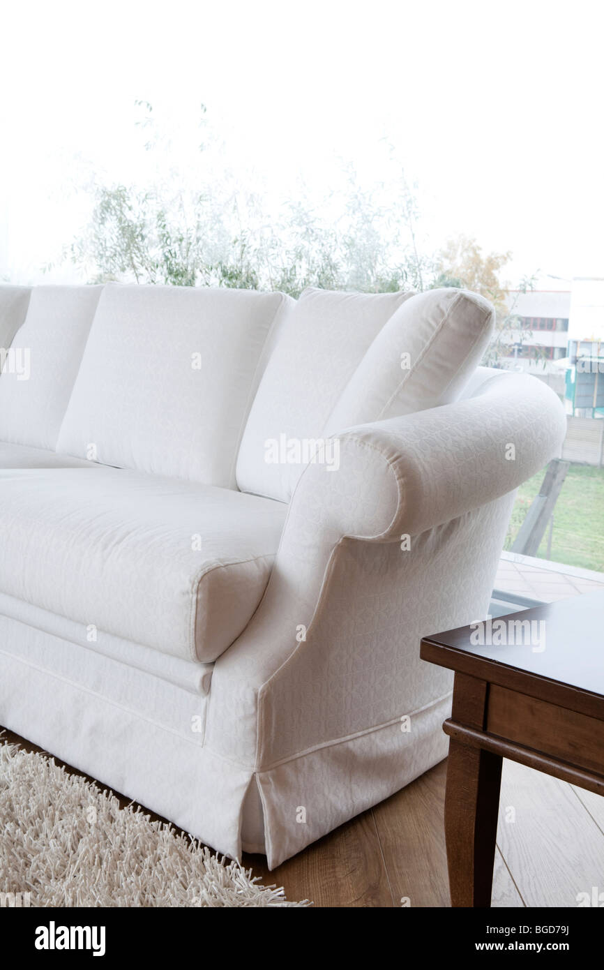 White Upholstered Sofa With Fringe Carpet And Coffee Table By The Window.  Living Room