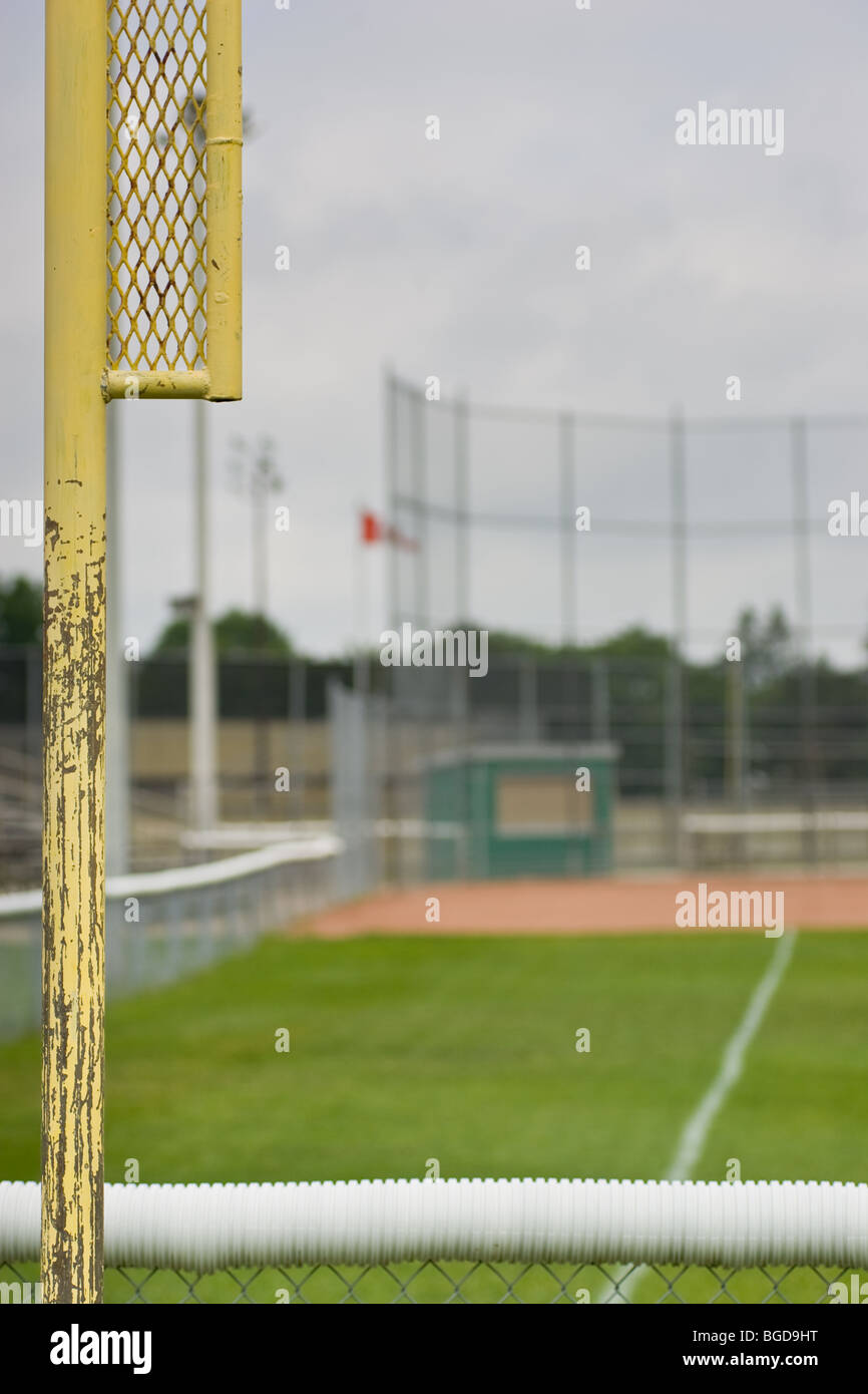 Behind the outfield fence, the foul line on the left, looking down the first base line towards an empty baseball - Stock Image