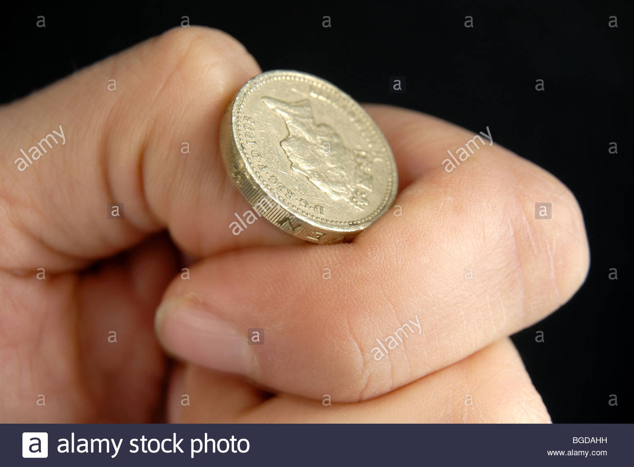 Flipping a UK pound coin. - Stock Image
