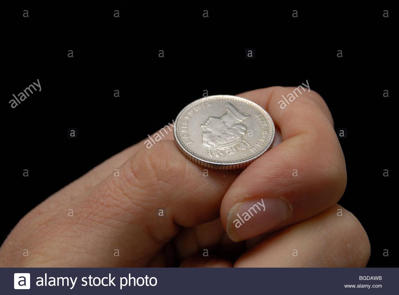 Flipping a ten pence piece coin. - Stock Image