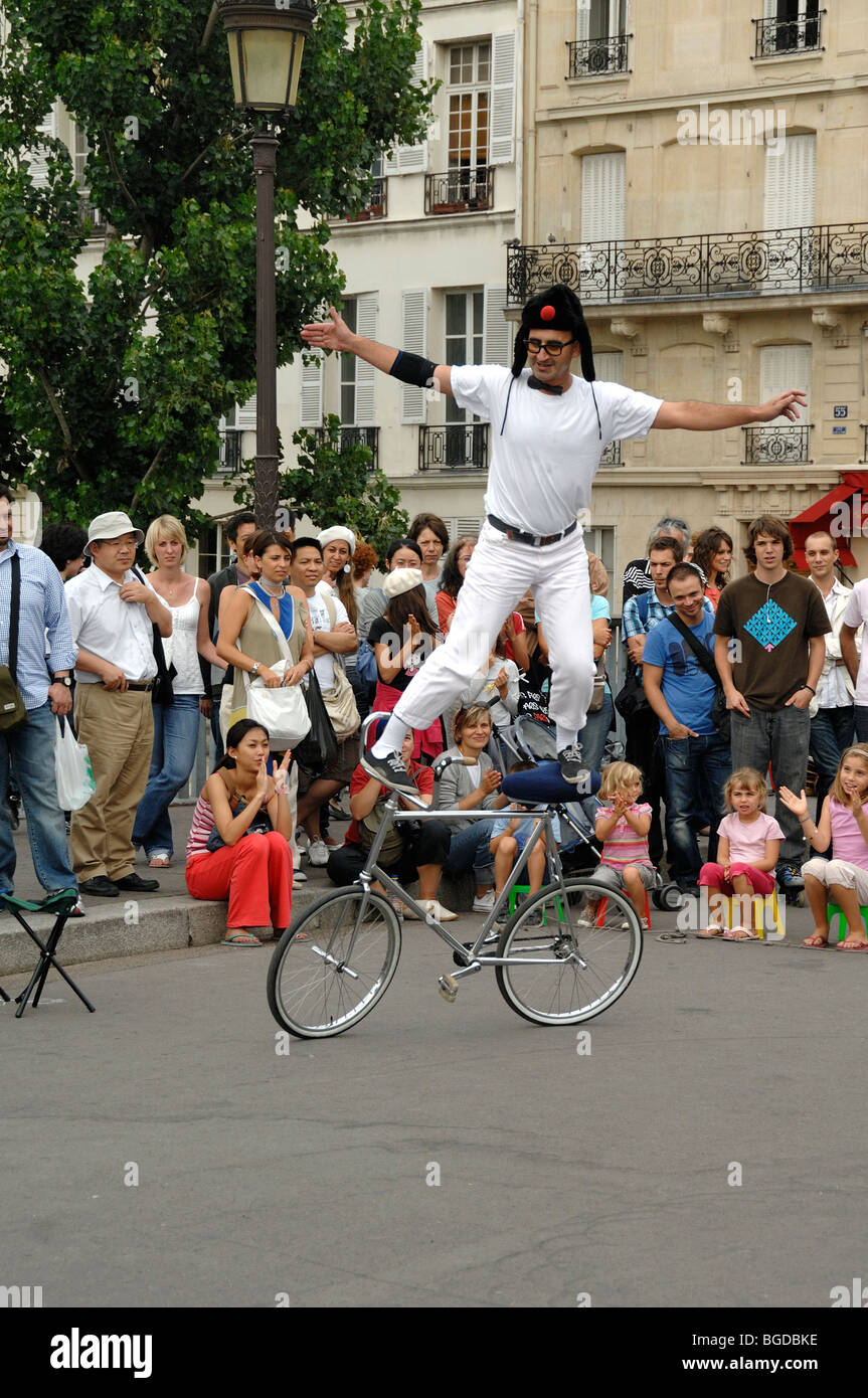 Street Theatre or Street Entertainer Balancing on Bicycle, Pont Saint Louis, Île Saint Louis, Paris, France - Stock Image
