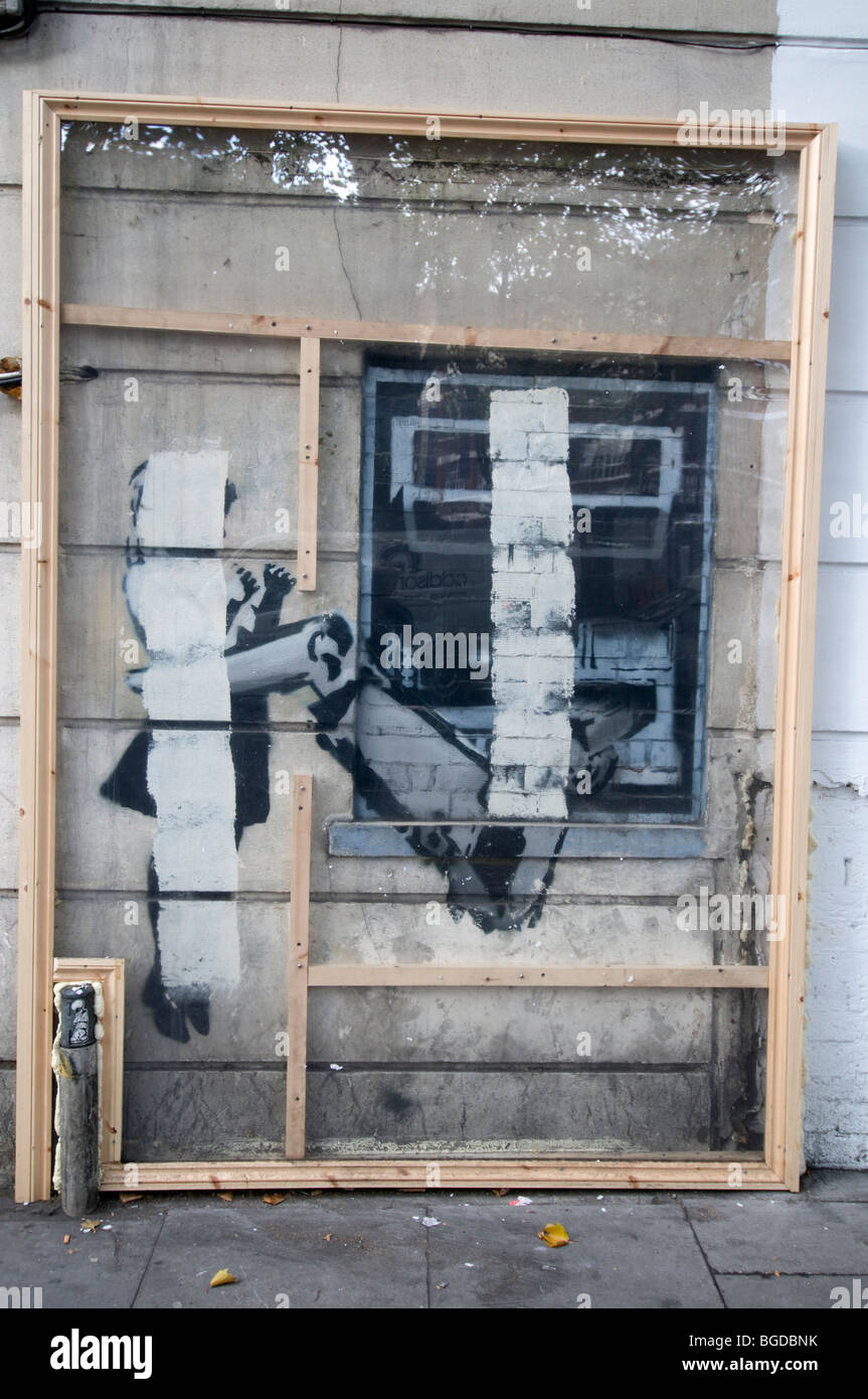 Banksy cash machine graffitti. Half painted out by the council, now in the process of being protected protected. - Stock Image