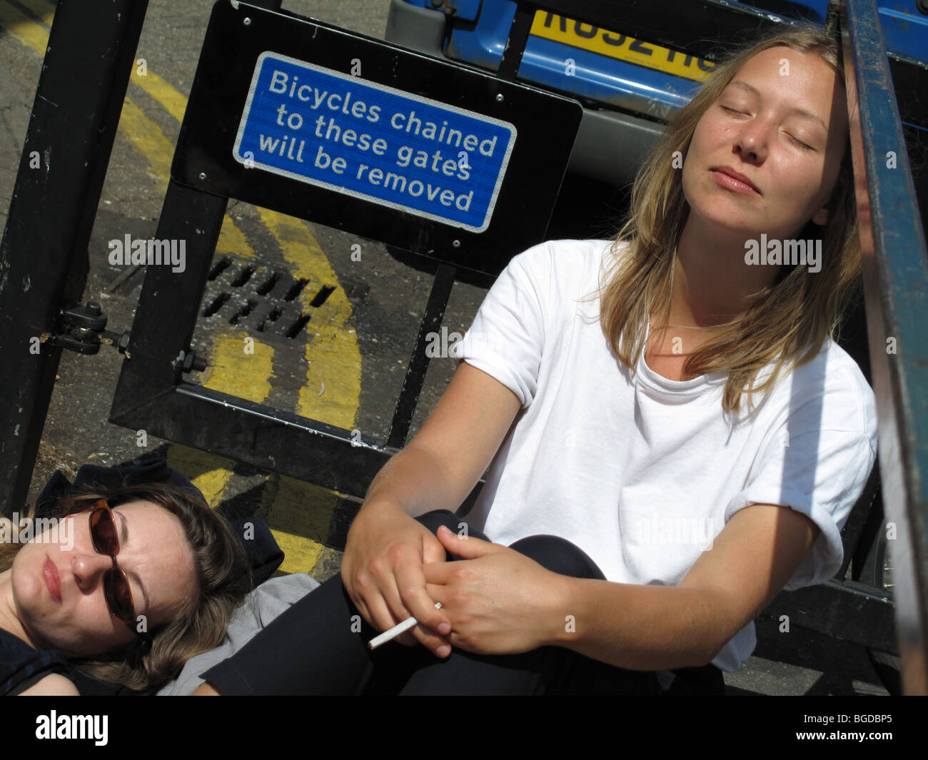 Broadway market , Hackney. Urban sunbathing. Two young women enjoy the sunshine. - Stock Image